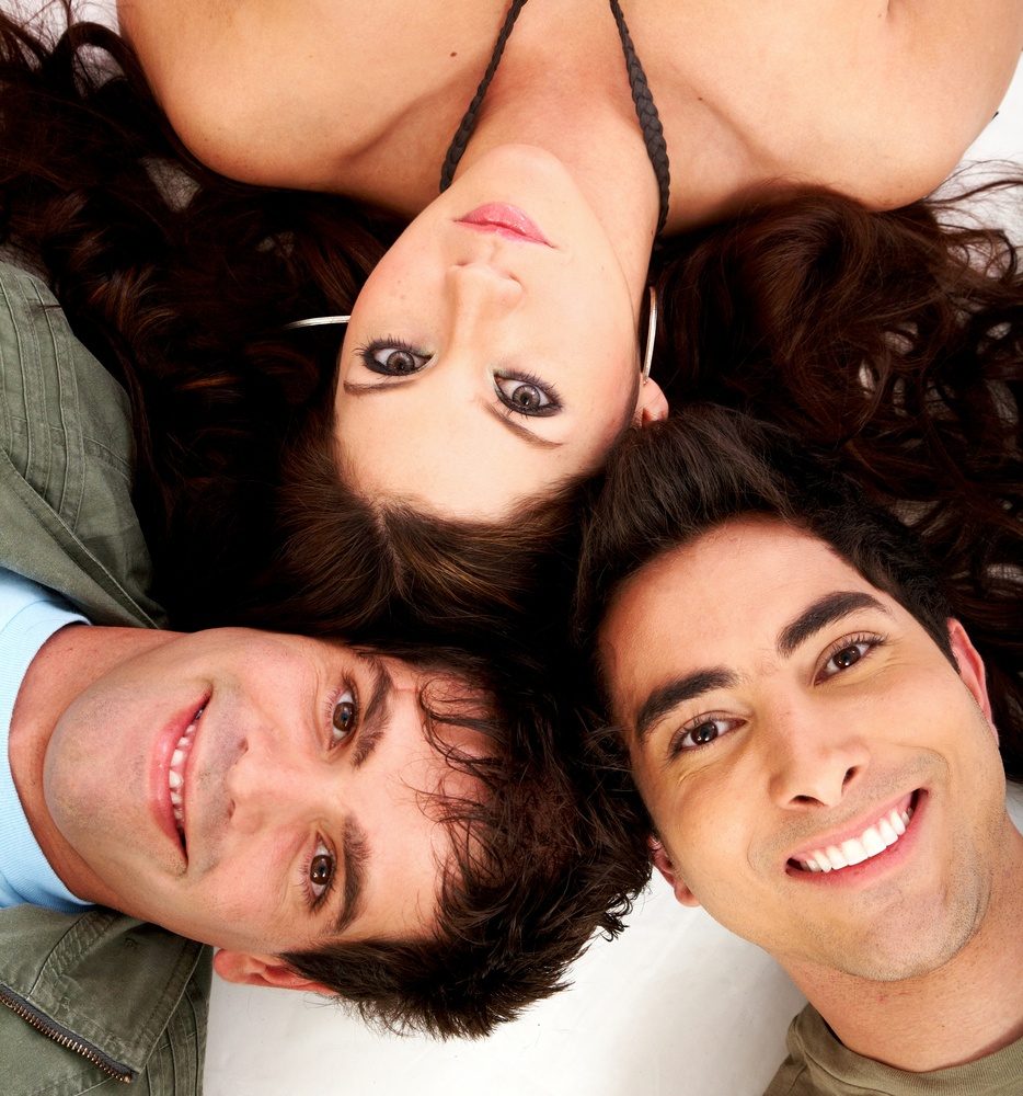 happy group of friends smiling in a love triangle with their heads together on the floor